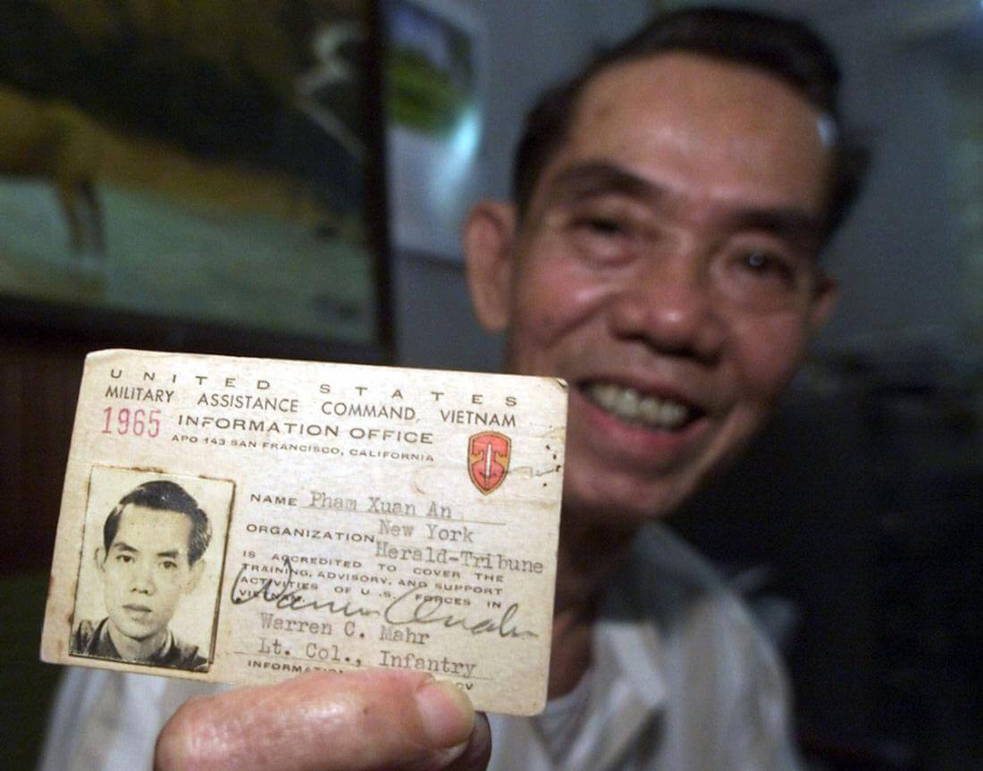 ** FILE ** Pham Xuan An holds up his press card from 1965 at his home in Ho Chi Minh City, Vietnam, in this April 26, 2000 file photo. Pham Xuan An, a Vietnamese who led a remarkable and perilous double life as a communist spy and a respected reporter for western news organizations during the Vietnam War, has died at a military hospital Wednesday, Sept. 20, 2006 in Ho Chi Minh City, his son said. An, 79, suffered from emphysema. (AP Photo/Charles Dharapak, File)