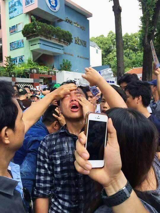 Đào Nguyên Anh đang được những người biểu tình khác giúp rửa mắt sau khi bị xịt hơi cay.